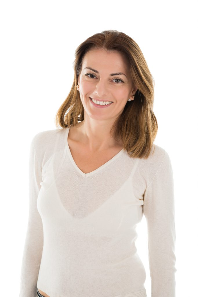 Portrait of beautiful mid adult woman in casuals standing against white background
