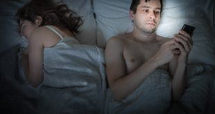 Young man is lying with girlfriend in bed and texting with phone at night. Insomnia and cheating concept.